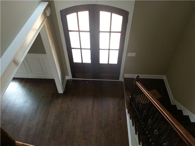 Lovely entry way with upscale trim, hardwoods, decorative staircase and contemporary entryway
